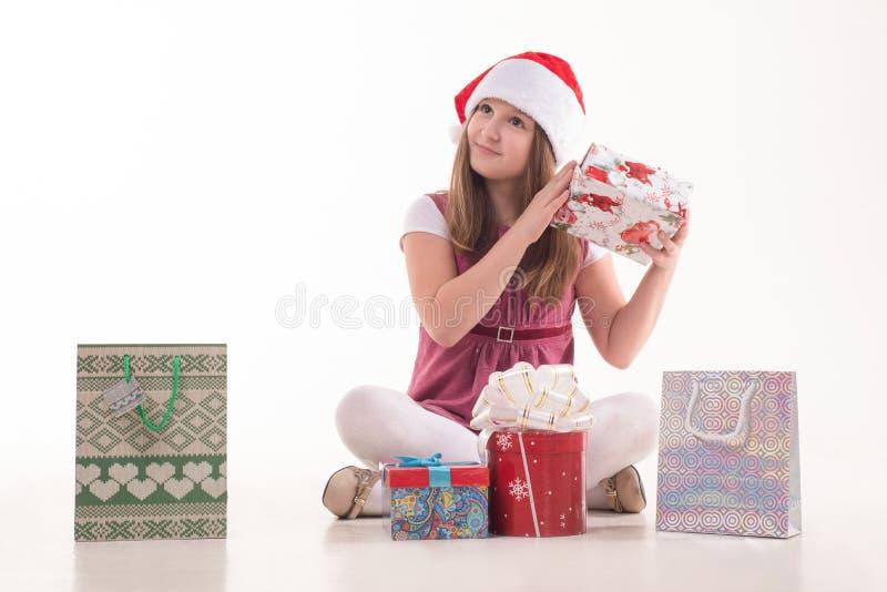Flickabarn med en gåva i en jultomtenhatt arkivfoton