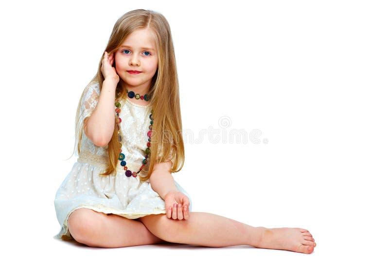 Flickabarn med långt blont hår som placerar på ett golv modeportr arkivbild