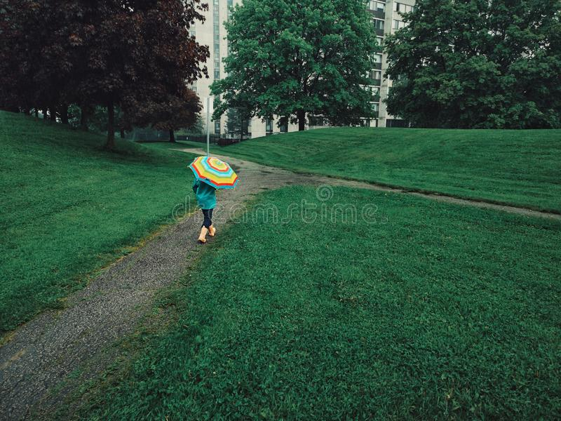 Flickabarn som går på gatavägen under regn med regnbågeparaplyet arkivbilder