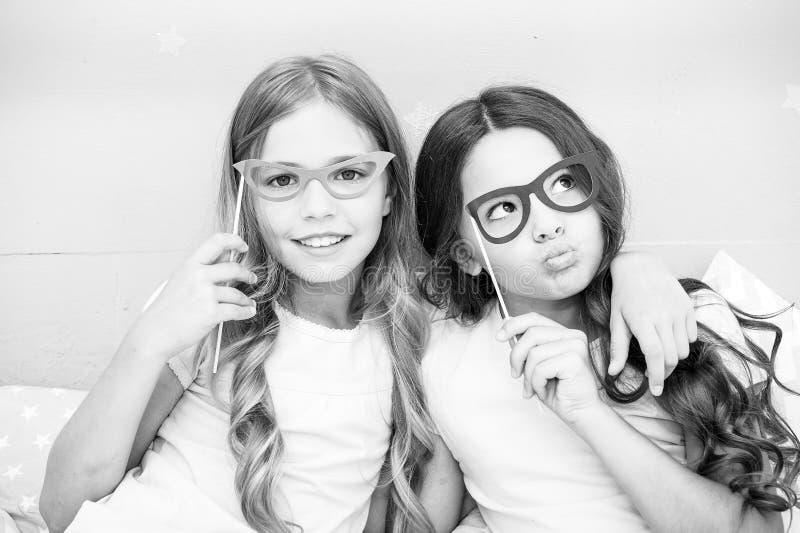 Flickabarn som poserar med stöttor för grimasfotobås Begrepp för pyjamasparti Flickavänner som har det roliga pyjamaspartiet arkivbild
