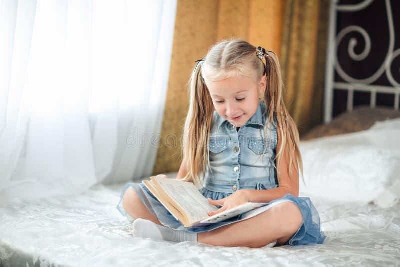 Flickabarnet i grov bomullstvillsundress lägger den säng lästa boken Ungen f?rbereder sig att g? att b?dda ned Angen?m tid i hemt royaltyfri foto