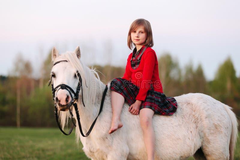 Flickabarnet sitter på en liten vit häst som ser in i kameran arkivfoto