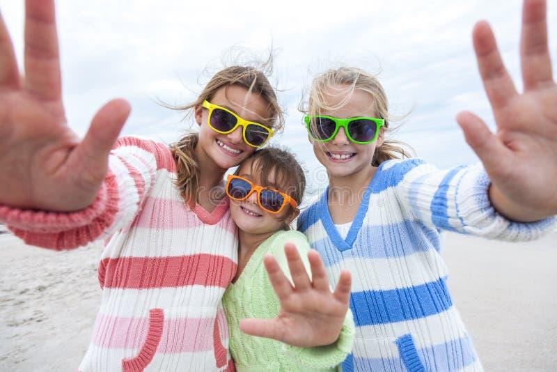 Flickabarnsystrar som spelar på stranden royaltyfria bilder