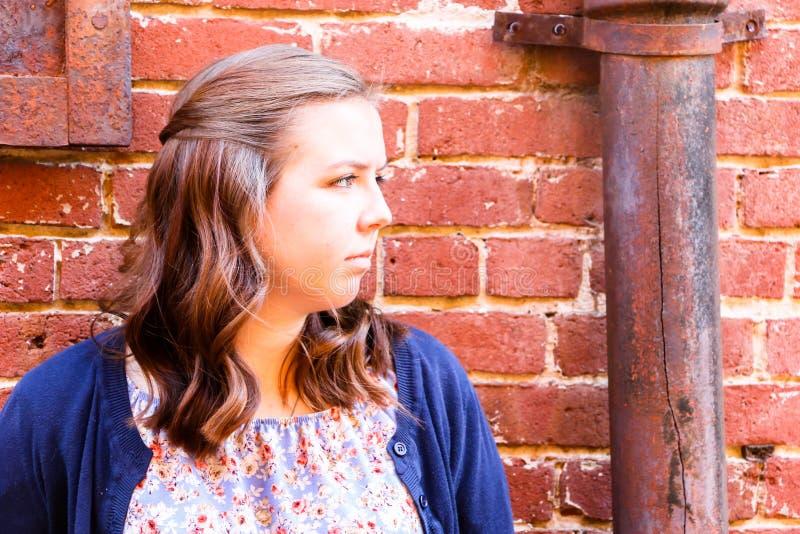 Flickabenägenhet mot väggen för röd tegelsten royaltyfri foto