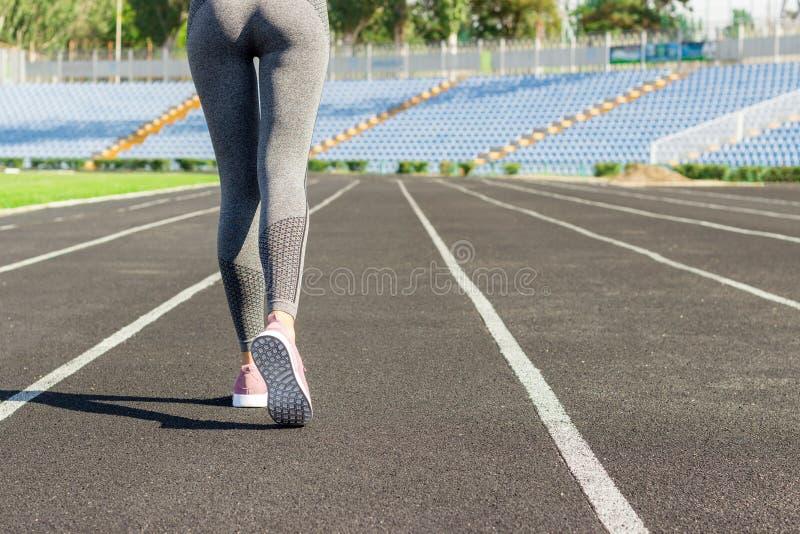 Flickaben i rosa sportskor som står på ett rinnande spår med stadionställningar Sportar och sunt begrepp fotografering för bildbyråer
