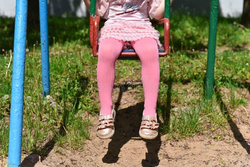 Flickaben i rosa strumpbyxor p? en gunga fotografering för bildbyråer