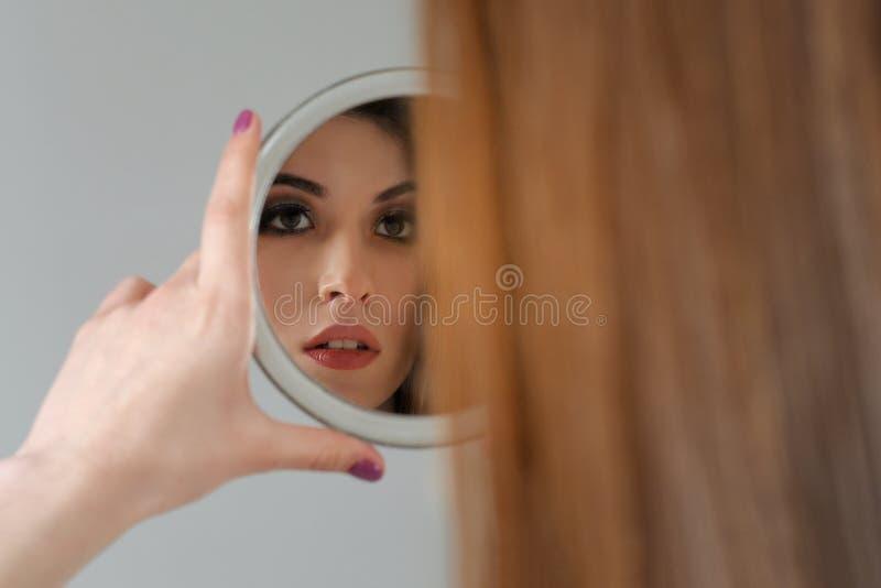 Flickablickar i den runda spegeln och ser i den hennes reflexion royaltyfri foto