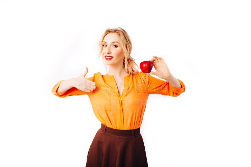 Flickablondinen i en ljus orange tröja med ett äpple i hennes händer främjar sund mat royaltyfri fotografi