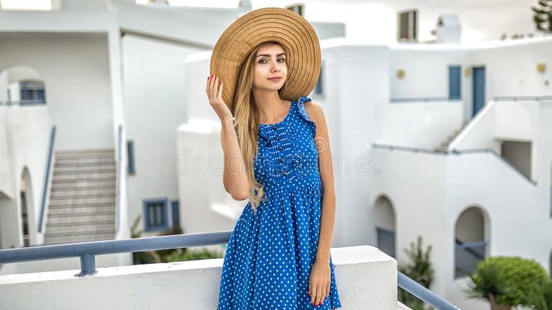 Flickablondinen med långt hår i en sugrörhatt i en blå klänning med prickar står i Santorini arkivfoton