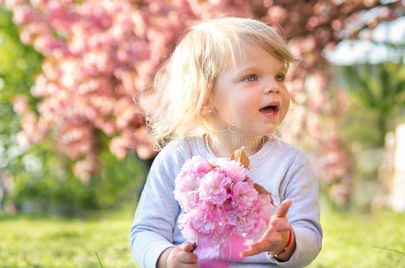 flickablondinen spelar med en kvist av sakura i en blommig sakura trädgård royaltyfri bild