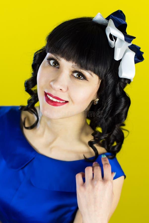 Flickabrunett i en blå klänning på en gul bakgrund arkivbild