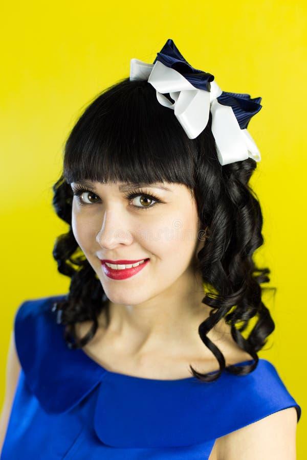 Flickabrunett i en blå klänning på en gul bakgrund fotografering för bildbyråer
