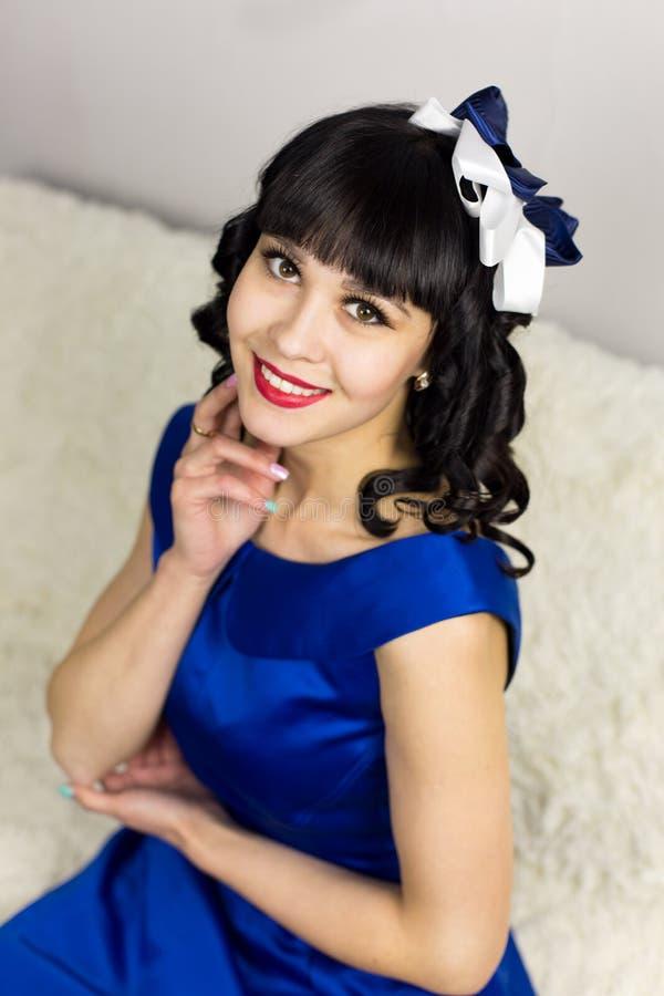 Flickabrunett i en blå klänning på en vit bakgrund arkivbild