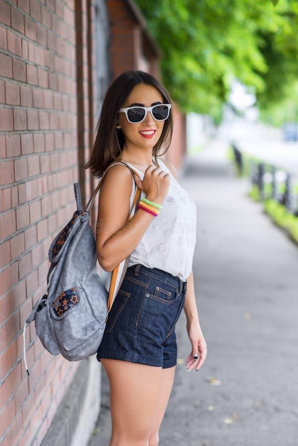 Flickabrunett i en parkera i sommaren som vilar den vita blusen på bakgrunden av trästaketet, modelivsstil som är försiktig arkivfoto