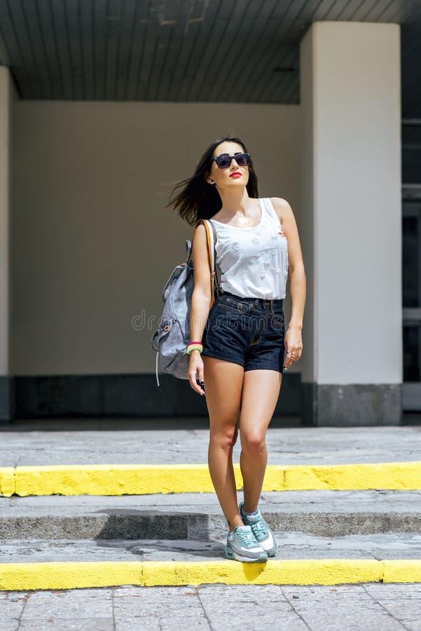 Flickabrunett i sommar i parkera med en ryggsäck som vilar i kortslutningar och vita blussolexponeringsglas, modelivsstil royaltyfria bilder