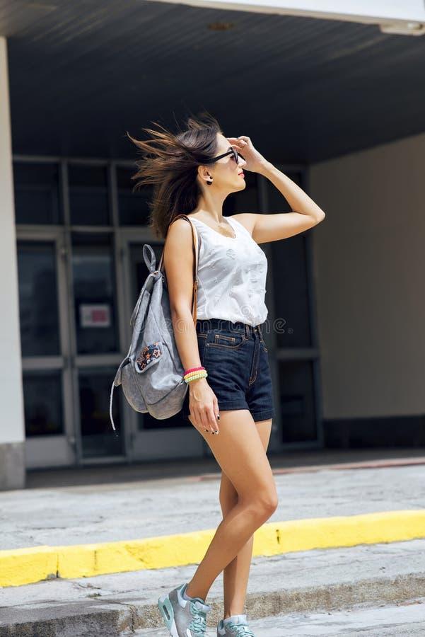 Flickabrunett i sommar i parkera med en ryggsäck som vilar i kortslutningar och vita blussolexponeringsglas, modelivsstil arkivbilder