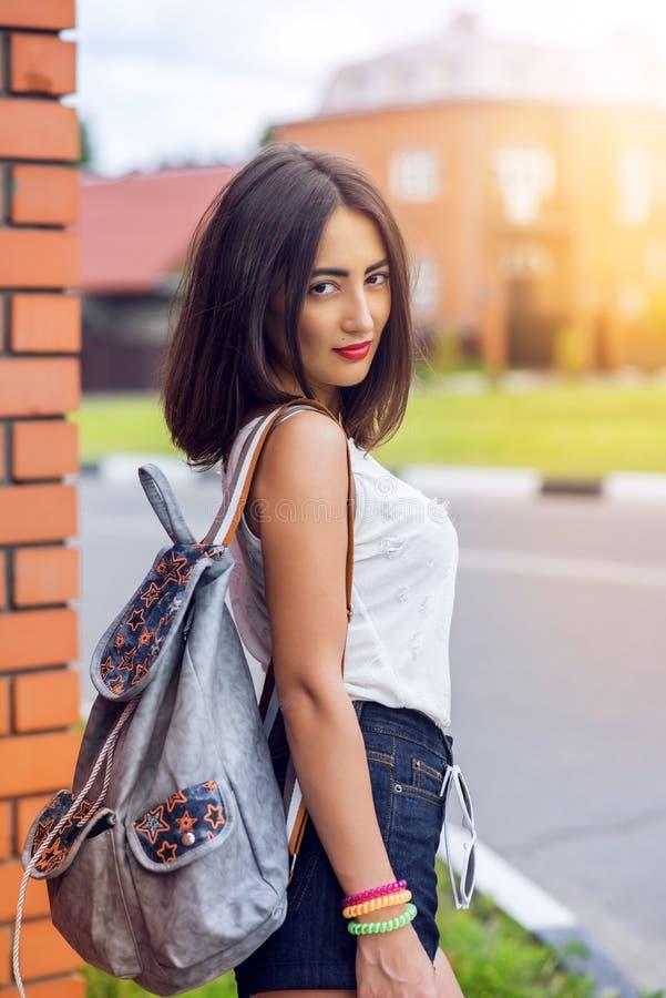Flickabrunetten i sommar i parkera med en ryggsäck som vilar i kortslutningar och den vita blusen, modelivsstil, stillar blick royaltyfri bild