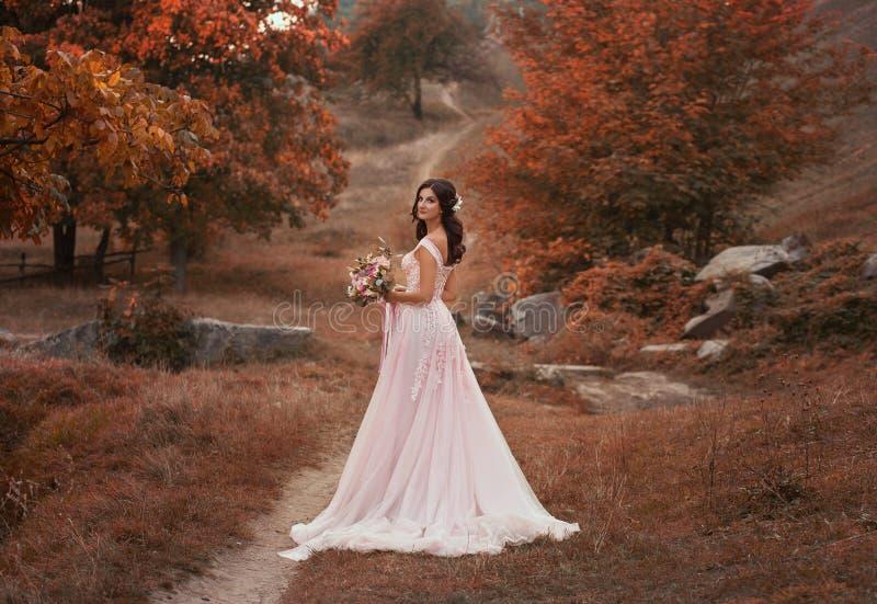 Flickabrunetten med långt hår, i en lyxig rosa färg klär med ett långt drev Bruden med en bukett poserar mot a royaltyfri foto