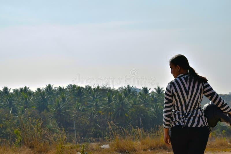 Flickacyklist som rymmer hennes hjälm och poserar för en bild i det breda landskapet arkivfoto