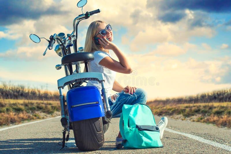 Flickacyklisten sitter på en motorcykel Koppla av efter turen royaltyfri foto
