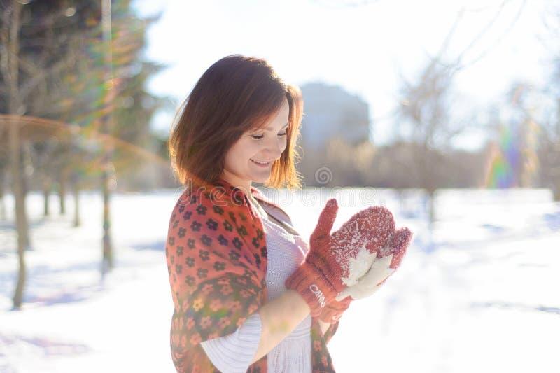 Flickadanande kastar snöboll i vinter royaltyfri bild