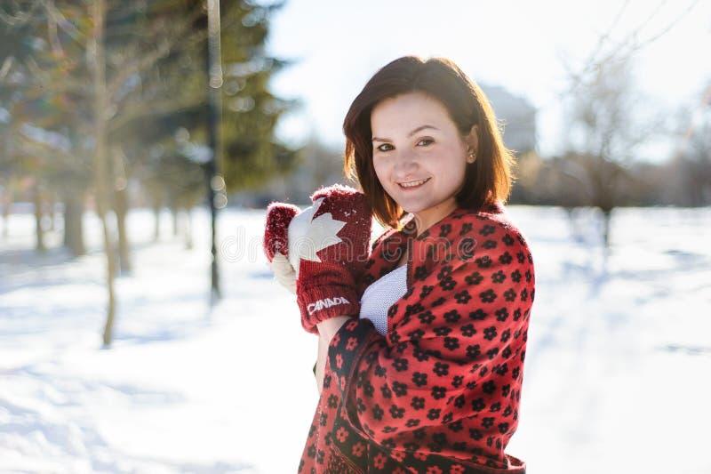 Flickadanande kastar snöboll och smiing in camera i vinter arkivbild