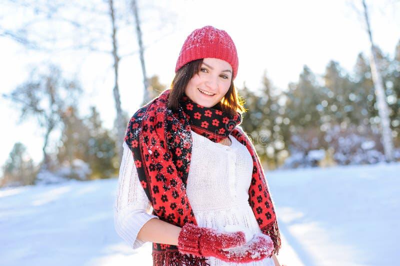 Flickadanande kastar snöboll och smiing in camera i vinter arkivfoto