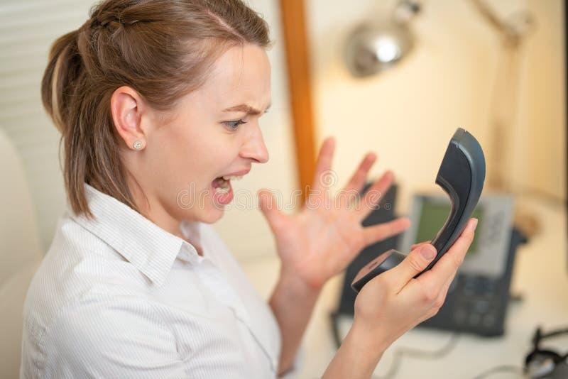 Flickadispatcherrop som arbetar med telefonen I appellmitten som är ilsken ondska royaltyfri bild