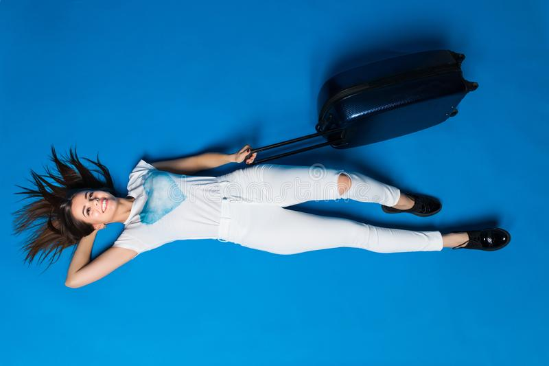 Flickadrömmar av en resa medan lögner på golvet på blå bakgrund Kvinna med bagage som ligger på isolerad bakgrund royaltyfria bilder