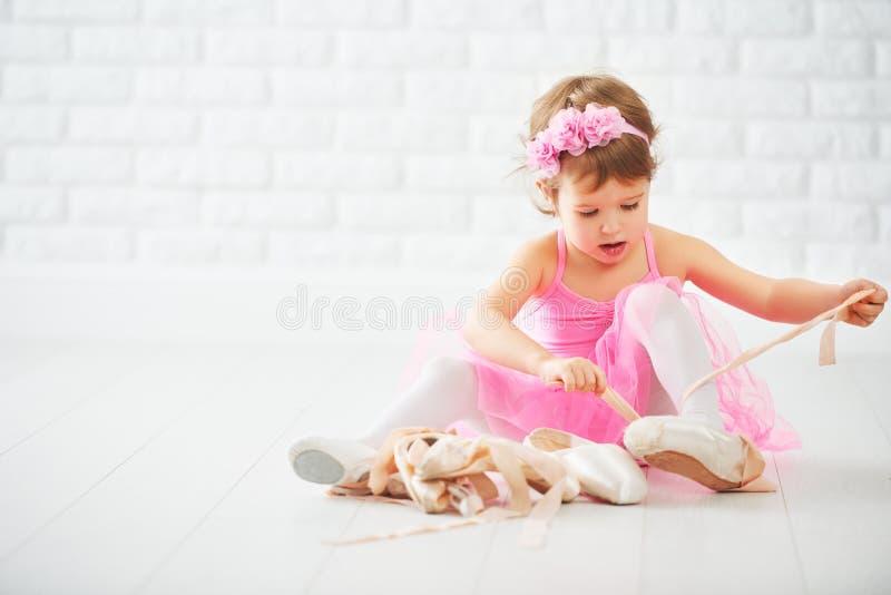 Flickadrömmar för litet barn av den passande ballerina med balettskon fotografering för bildbyråer