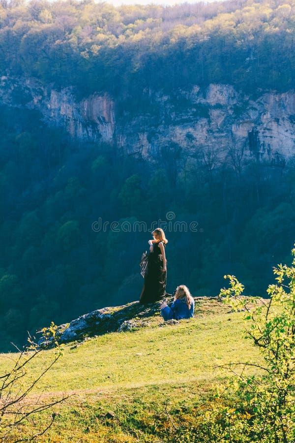 Flickafotografen som fotograferar en modell i en svart klänning på, vaggar utomhus och träna på en vårdag royaltyfri fotografi