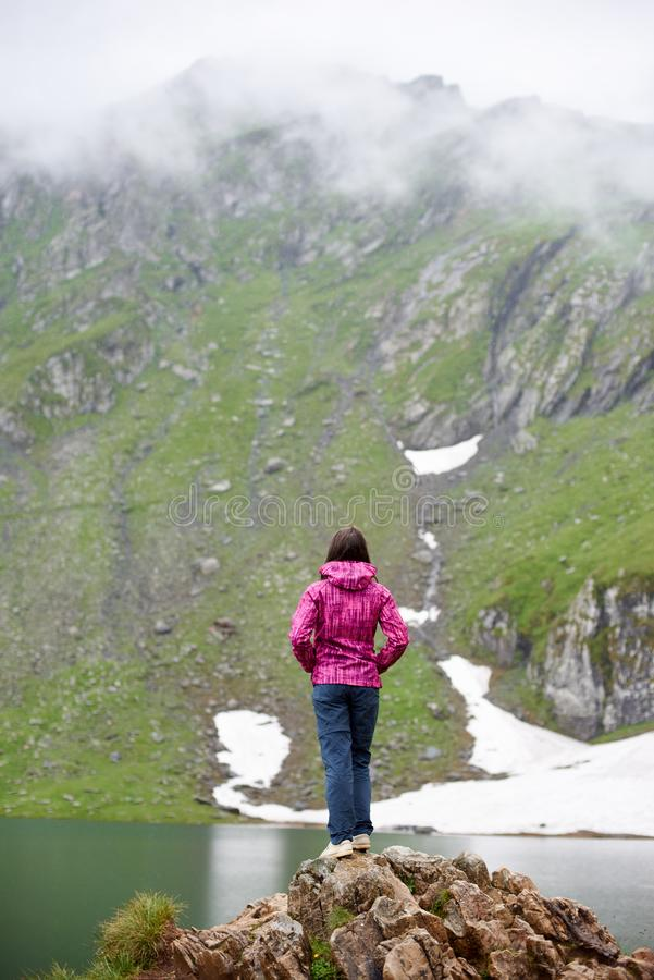 Flickafotvandrareanseende på kanten av den steniga klippan arkivbild