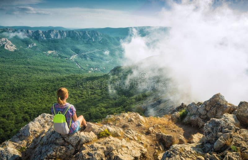 Flickafotvandraren tycker om de dimmiga bergen royaltyfria bilder