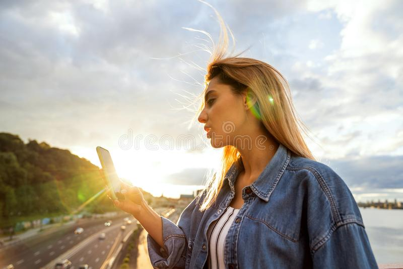 Flickafreelancer som arbetar med telefonen på solnedgången arkivbilder