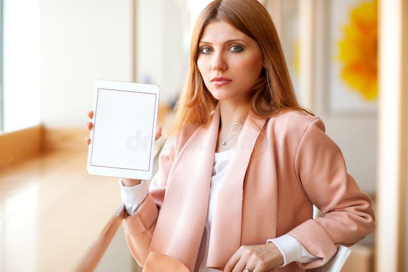 Flickafreelancer som rymmer en minnestavla i kaf?t arkivbild
