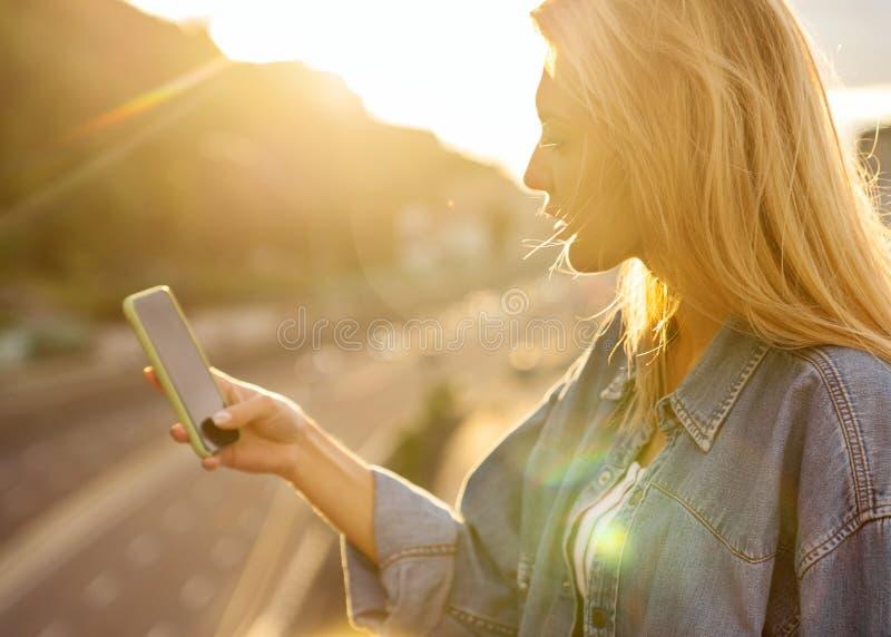 Flickafreelanceren på solnedgången talar på telefonen och arbetar royaltyfri foto