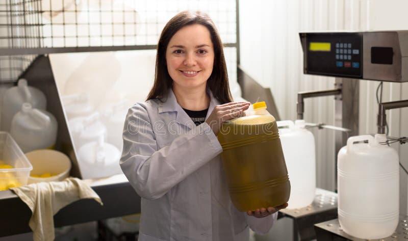 Flickafyllningflaskor med olivolja arkivbild