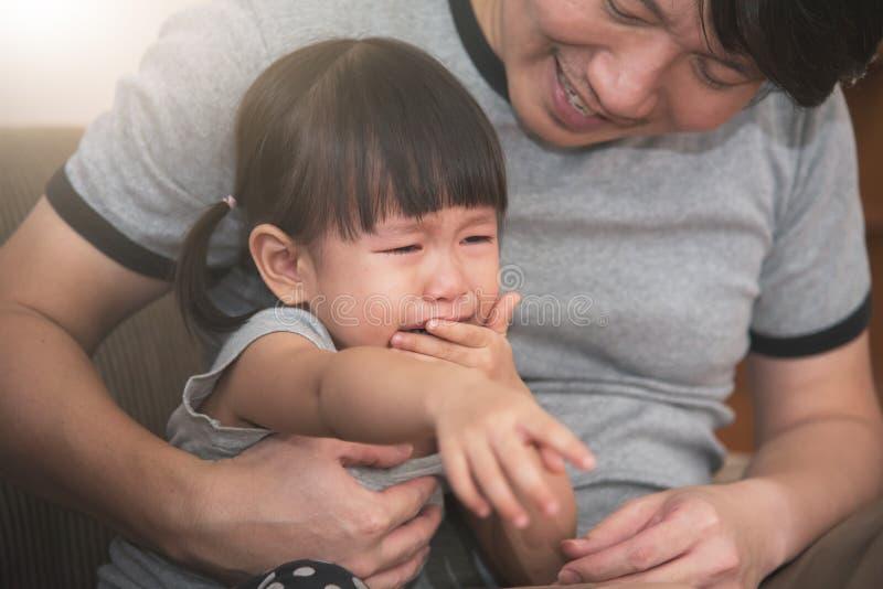 flickagråt för liten unge medan trösta för fader arkivbild