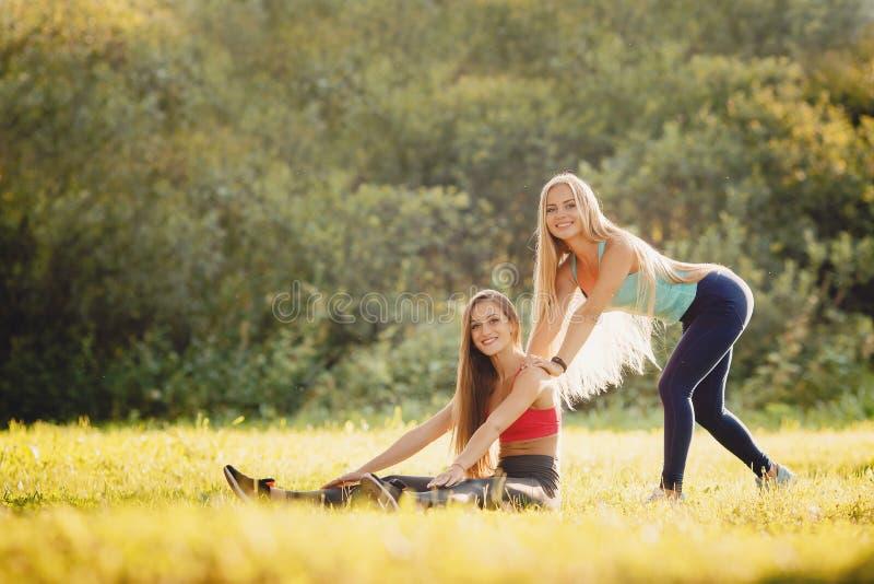 Flickagruppen av vändrevet i parkerar med yoga och kondition arkivfoto