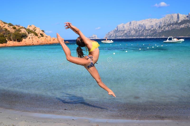 Flickagymnast, hopp, Sardinia, Porto Istana strand som vänder mot ön av Tavolara arkivbilder