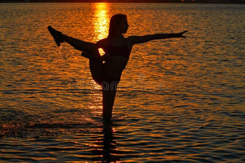 Flickagymnastik poserar på solnedgångstranden royaltyfria foton