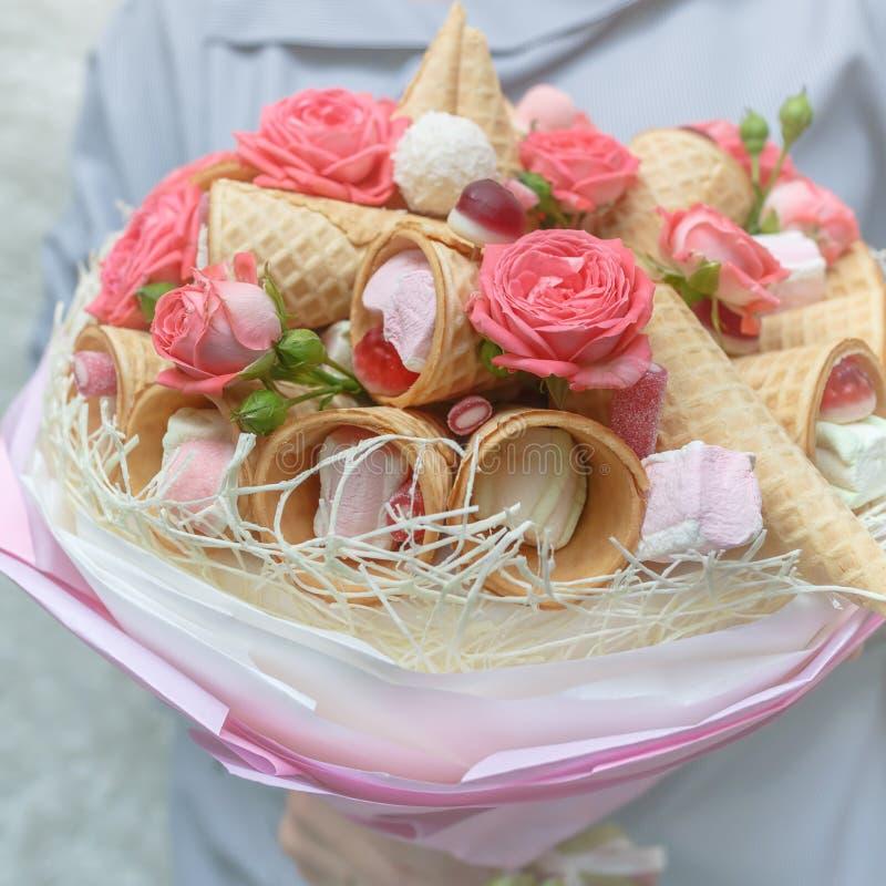 Flickahåll i hennes händer en original- bukett som består av rosa blommor av en ros och olika sötsaker på en ljus bakgrund royaltyfri bild