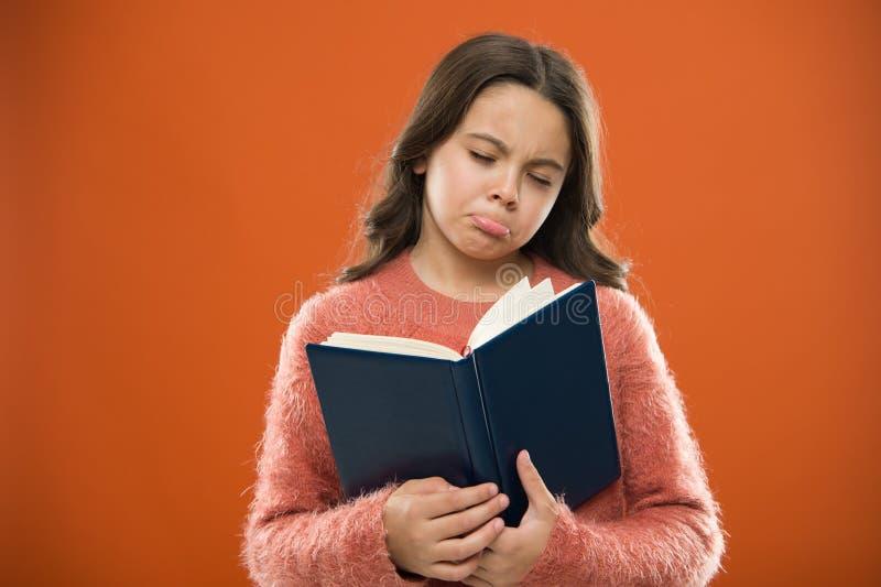 Flickahållboken läste berättelse över orange bakgrund Barnet tycker om läseboken Begrepp för boklager Underbara fria barn arkivbilder