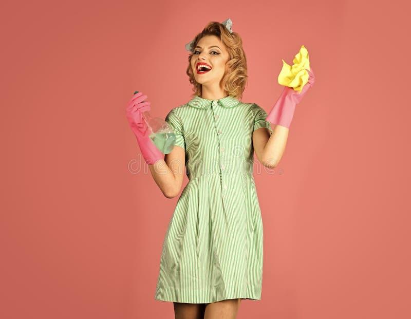 Flickahållen i händerna en dammtrasa och en tvål buteljerar arkivfoto