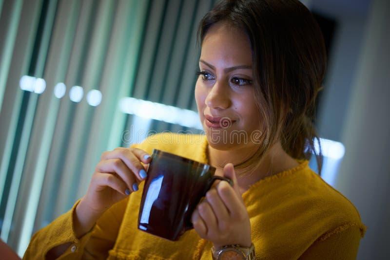 Flickahögskolestudent Drinking Coffee Studying på natten royaltyfria bilder