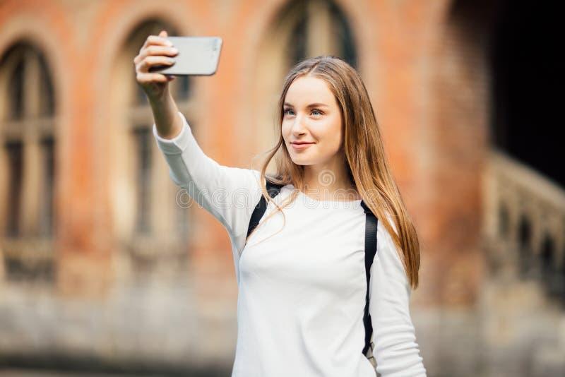 Flickahögskolestudentsammanträde utanför byggnad och ta en selfie på universitetsområdebakgrund arkivfoton