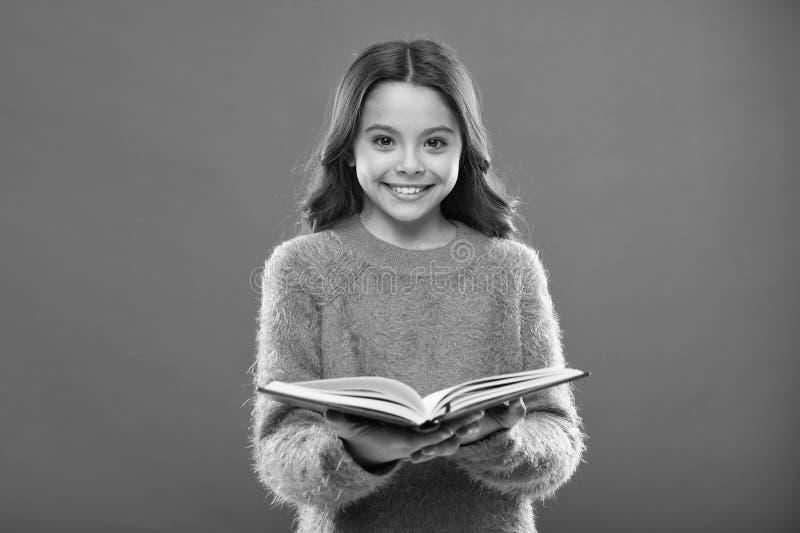 Flickah?llboken l?ste ber?ttelse ?ver orange bakgrund Barnet tycker om l?seboken Begrepp f?r boklager Underbara fria barn arkivbild