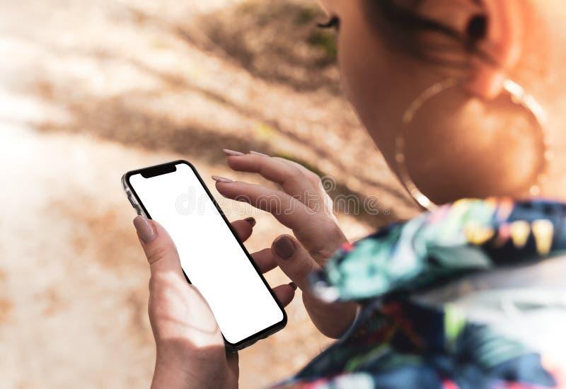 Flickahand som rymmer den svarta smartphonen med den stora tomma skärmen arkivbild