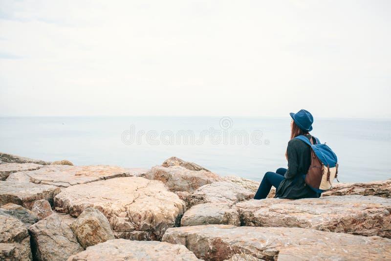 Flickahandelsresande i en hatt med en ryggsäck bredvid havet som ser in i avståndet Loppet vilar och att fotvandra, frihet royaltyfri fotografi