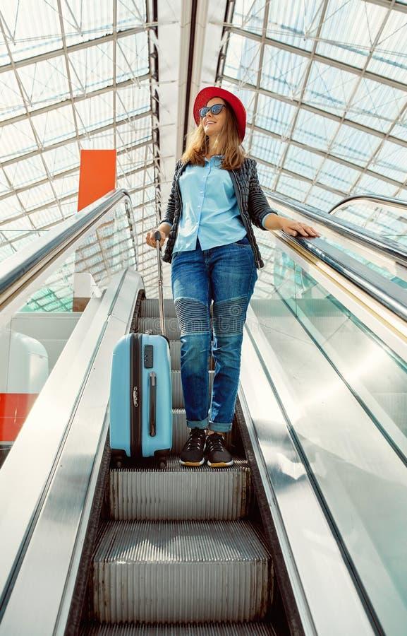 Flickahandelsresande med resväskan på rulltrappan i flygplats royaltyfri fotografi